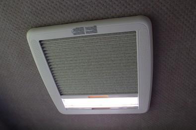 Střešní okno minikaravanu se zatahovací zatemňovací roletou. Minkaravan Tomplan od Tanatechu.