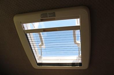 Střešní okno minikaravanu se zatahovací sítí proti hmyzu.