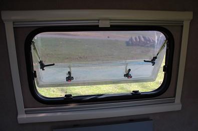 Boční okno minikaravanu se zatahovací síťkou proti hmyzu a zatemňovací roletou. Minikaravan TOMPLAN od Tanatechu.