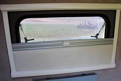 Boční okno minikaravanu se sítí proti hmyzu a zatemňovací roletou. Minikaravan Tomplan od Tanatechu.