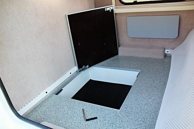 Pod spací matrací je úložný prostor v podlaze přívěsu. Minikaravan Tomplan od Tanatechu.