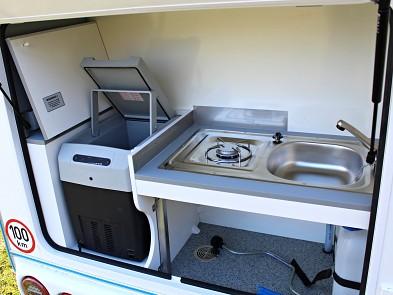 Kuchyně v karavanu Tomplan od Tanatechu obsahuje elektrickou lednici, plynový vařič a dřez.